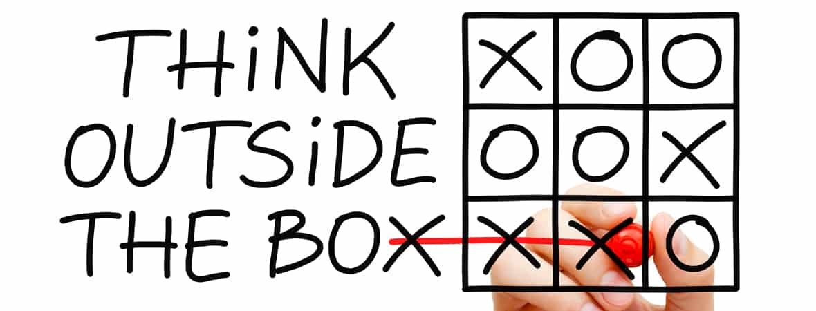 Hand sketching Think Outside The Box tic-tac-toe game concept with marker on transparent wipe board.